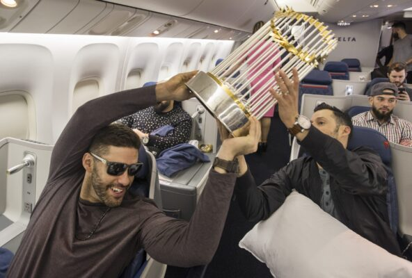 Somewhere between Los Angeles and Boston-- October 29, 2018-Stan Grossfeld/ Globe Staff—J.D. Martinez hands the World Series trophy off to Joe Kelly on the  Red Sox charter on the way back from winning the World Series in Los Angeles.