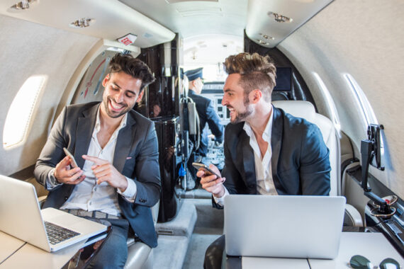 Young well dressed businessmen sitting inside private airplane and working on their mobile devices during business flight. Cockpit with pilot is seen in the background.